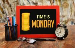 Il tempo è denaro concetto con le monete di oro e l'orologio di tavola Immagine Stock
