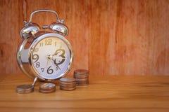 Il tempo è denaro concetto: La sveglia ha messo sopra la tavola di legno con la pila di baht d'argento delle monete dei soldi in  Fotografie Stock