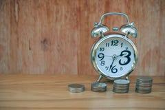 Il tempo è denaro concetto: La sveglia ha messo sopra la tavola di legno con la pila di baht d'argento delle monete dei soldi in  Immagine Stock Libera da Diritti