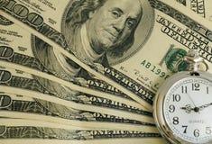 Il tempo è i soldi Lle banconote di cento dollari sotto l'orologio Immagini Stock Libere da Diritti