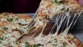 Il tempo alla pizzeria, uomo del pasto che prende una fetta della pizza ha sparato con profondità di campo molto sottile Pagina F archivi video