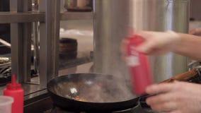 Il tempo del cuoco che cucina la pasta aggiunge la salsa dalla bottiglia e dalle scalpore stock footage