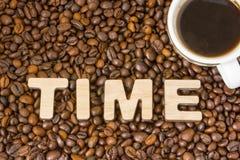 Il tempo di parola composto di grandi lettere con la struttura di legno è situato sui precedenti dei chicchi di caffè con una taz Fotografia Stock Libera da Diritti