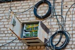 Il tempo ha sigillato la scatola con il commutatore a fibra ottica disposto sulla parete della costruzione di appartamento immagini stock