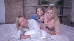 Il tempo libero della famiglia con la madre, la mamma felice si diverte con belle figlie sdraiate a letto mentre si riposano a ca video d archivio