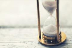 Il tempo sta ticchettando - clessidra sulla tavola con lo spazio della copia Immagini Stock