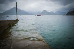 Il tempo tempestoso e un canottaggio sommerso si mettono in bacino in Elgol sull'isola di Skye in Scozia Fotografie Stock