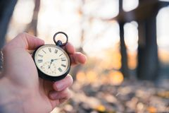 Il tempo va vicino: aria aperta d'annata dell'orologio, tenuta in mano; legno e foglie immagini stock