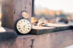 Il tempo va vicino: aria aperta d'annata dell'orologio, tenuta in mano; legno e foglie immagine stock libera da diritti