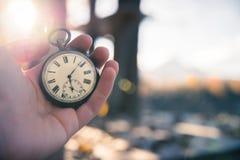 Il tempo va vicino: aria aperta d'annata dell'orologio, tenuta in mano; legno e foglie immagini stock libere da diritti
