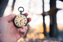 Il tempo va vicino: aria aperta d'annata dell'orologio, tenuta in mano; legno e foglie immagine stock