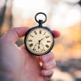 Il tempo va vicino: aria aperta d'annata dell'orologio, tenuta in mano; legno e foglie fotografia stock