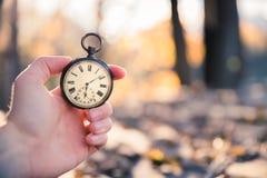 Il tempo va vicino: aria aperta d'annata dell'orologio, tenuta in mano; legno e foglie fotografie stock