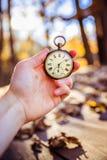 Il tempo va vicino: aria aperta d'annata dell'orologio, tenuta in mano; legno e foglie fotografia stock libera da diritti