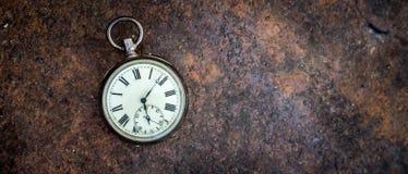 Il tempo va vicino: orologio d'annata su una terra del metallo fotografia stock
