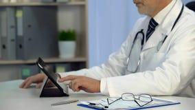 Il terapista controlla le cartelle sanitarie elettroniche sulla compressa, le tecnologie, sanità immagini stock