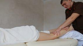 Il terapista di massaggio esegue la procedura per le gambe delle ragazze sullo strato in ufficio luminoso video d archivio