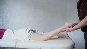 Il terapista di massaggio esegue la procedura per le gambe delle ragazze sullo strato in ufficio luminoso archivi video