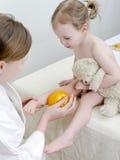 Il terapista fa un massaggio del bambino Immagini Stock
