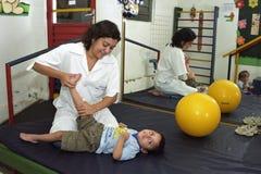 Il terapista femminile lavora con il bambino handicappato, Brasile Fotografie Stock Libere da Diritti