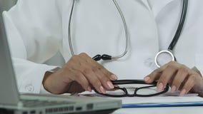Il terapista femminile passa gli occhiali della tenuta, email della lettura del medico sul computer portatile stock footage