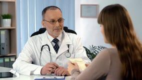 Il terapista ha dato la prescrizione al paziente, prezzi della lettura della donna per il trattamento fotografia stock libera da diritti