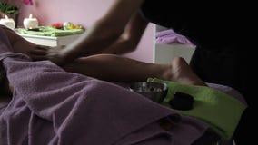Il terapista maschio applica l'olio sul corpo della donna nel centro della stazione termale video d archivio