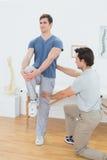 Il terapista maschio che assiste il giovane con l'allungamento si esercita Fotografie Stock