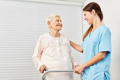 Il terapista si preoccupa per le donne anziane con il camminatore immagini stock libere da diritti