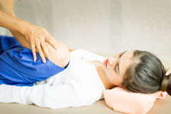 Il terapista tailandese di massaggio sta piegando una gamba delle donne Immagine Stock Libera da Diritti