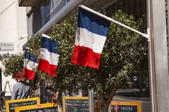 Il terrazzo francese del caff? pilota i tri colori davanti al ristorante ed al negozio Immagine esterna con le sedie, le tavole,  immagine stock libera da diritti