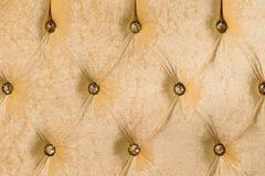 Il tessuto beige del primo piano ha ricoperto la testata con il fondo del tessuto dei bottoni, retro mobilia alla moda della came immagini stock libere da diritti