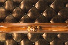 Il tessuto dell'oro del primo piano ha ricoperto la testata con il fondo del tessuto dei bottoni, retro mobilia alla moda della c immagini stock
