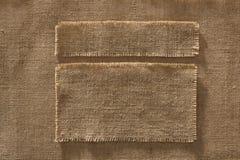 Il tessuto della tela da imballaggio incornicia le etichette dei pezzi, toppa del panno di tela su tela di iuta immagini stock libere da diritti