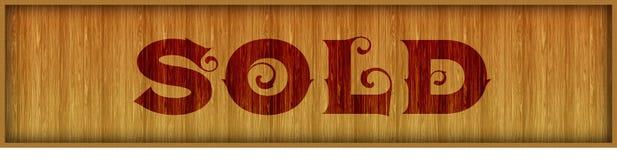 Il testo d'annata della fonte HA VENDUTO sul fondo di legno quadrato del pannello Fotografia Stock