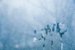 Il testo di amore attinge la finestra della gocciolina della mattina nebbiosa fredda Fotografie Stock Libere da Diritti