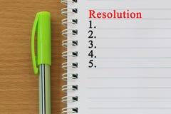 Il testo di risoluzione e dei taccuini è disposto su un floo di legno marrone Fotografia Stock