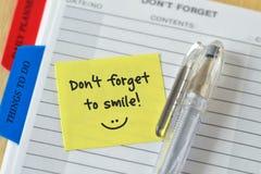 Il testo indossa il ` t dimentica al sorriso scritto su una nota appiccicosa sopra Agen immagini stock libere da diritti