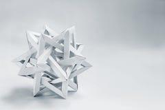 Il tetraeder complesso ha piegato gli origami di carta su un fondo bianco fotografia stock