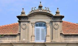 Il tetto della costruzione con squisito intaglia e finestra blu Immagini Stock Libere da Diritti