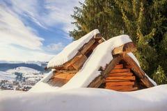 Il tetto della montagna coperta di casa della neve Immagini Stock