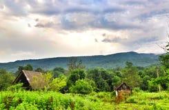 Il tetto delle montagne abbandonate della casa nei precedenti fotografie stock