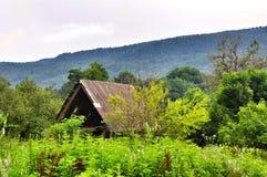 Il tetto delle montagne abbandonate della casa nei precedenti fotografia stock