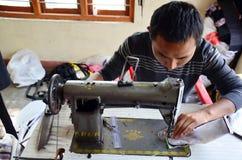 Il tibetano dell'uomo cuce il cotone tramite la macchina per cucire ai campi profughi tibetani Fotografie Stock Libere da Diritti