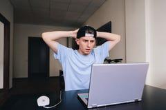Il timore del twith dello studente esamina il monitor del suo computer mentre si siede alla tavola nella sua aula magna Immagine Stock Libera da Diritti