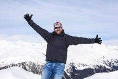 Il tipo è felice di essere nelle montagne nevose Fotografia Stock