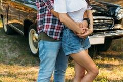 il tipo è indietro ed abbraccia la ragazza, mani insieme dietro è un'automobile nera tenendosi per mano di estate sulla mano di u fotografie stock