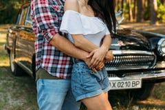 il tipo è indietro ed abbraccia la ragazza, mani insieme dietro è un'automobile nera tenendosi per mano di estate sulla mano di u fotografia stock libera da diritti