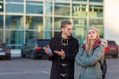 Il tipo è indignato alla ragazza a causa dello smartphone rotto, la ragazza ha girato il suo fronte offendedly Fotografia Stock