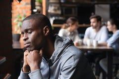 Il tipo africano triste ritiene la seduta sola da solo in caffè fotografie stock